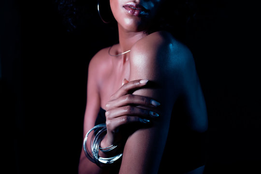 Young unrecognizable lady seductively strokes body. Beautiful girl touching her forearm. Hand with fashionable bracelets. Jewelry, fashion, healthy skin concept.
