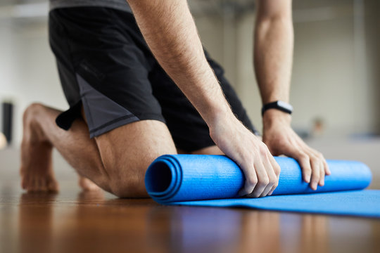 Close-up of unrecognizable man standing on knees and rolling out exercise mat after yoga training in gym