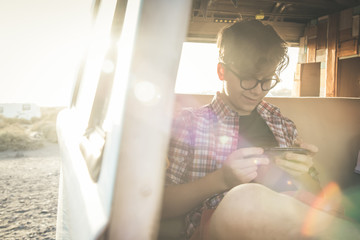 Young handsome guy sitting in a car watching smiling focused phone, playing with electronic device Chatting with friends away connect everywhere View from outside the door of a vintage van