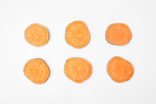 Composition with slices of sweet potato on white background, top view
