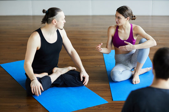 Content flexible young people in sportswear sitting on blue exercise mats and talking to each other while waiting for yoga class