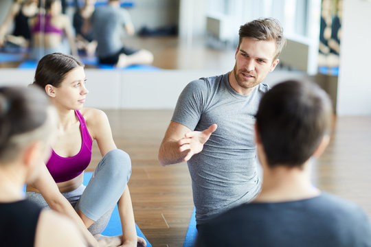 Serious pensive sporty guy with stubble sitting on floor and gesturing hand while sharing ideas for good training at yoga class