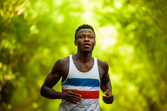 young athletic and attractive black afro American runner man doing running workout training outdoors on urban city park in fitness sport and wellness