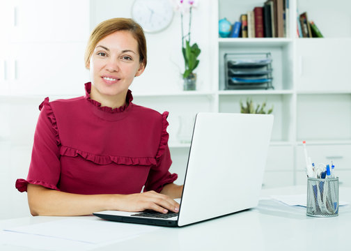 Woman sitting at office and working with laptop
