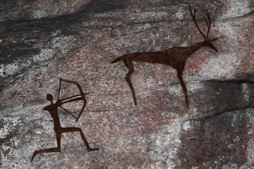 The image on the wall of the cave of an ancient hunter and animal . ancient history.