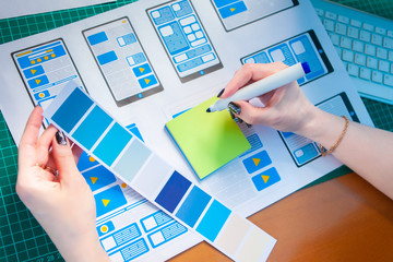 Girl graphic designer selects the color for the design of the mobile application. Office of the designer. ux Graphic designer sketch for web mobile phone. Test and Discuss New App Features.