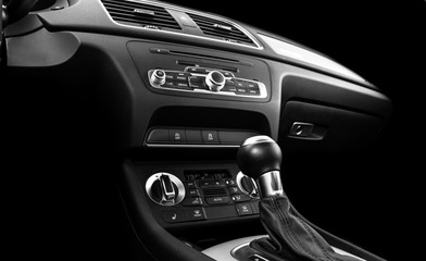 Modern Luxury car inside. Interior of prestige car. Black Leather. Car detailing. Dashboard. Media, climate and navigation control buttons. Sound system. Modern car interior details. Black and white