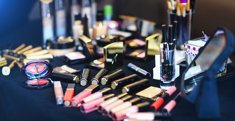 Amazing set of cosmetic products lie on table. Real make up brushes of professional beautician. Makeup kit for wedding or fashion events. Multi-colored lipstick collection.