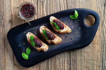 open sandwiches with kalamata olives paste decorated with basil leafs on black serving board with a glass jar of the paste