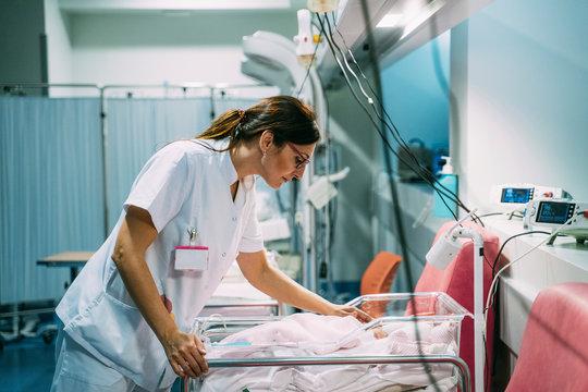 Female doctor examining newborn baby in the hospital. Night shift