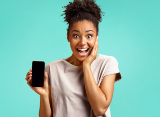 Overjoyed girl shows screen smartphone. Photo of african american girl wears casual outfit on turquoise background. Emotions and pleasant feelings concept.