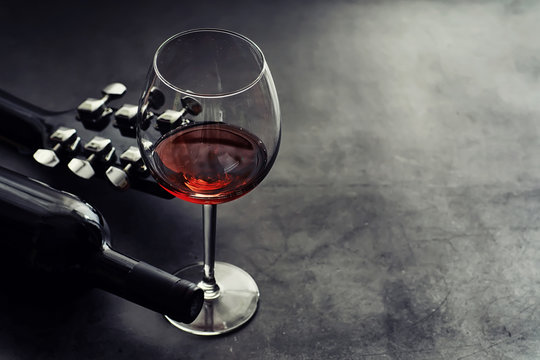 Guitar and high glass with red wine on a stone background.