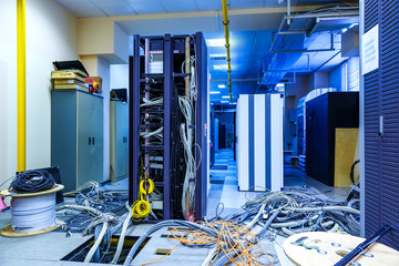 Server room with racks in datacenter and internet problem causing by disorder of wiring.