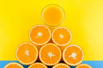 Cut halves of juicy orange on yellow blue background. Orange fruit, citrus minimal concept....