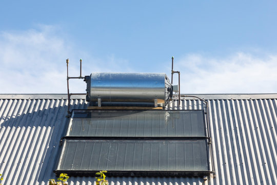 Rooftop solar hot water cylinder with photovoltaic cells  on domestic house converting renewable solar energy for heating and electricity