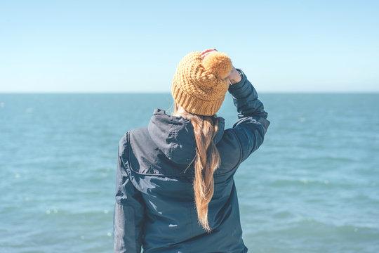 Defocused figure woman rear view on the sea watching the waves