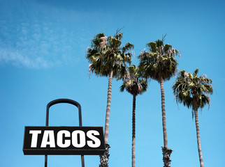 aged and worn tacos sign with palm trees