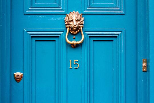 House door number fifteen with the 15 in bronze on a turquoise door with lion head door knocker