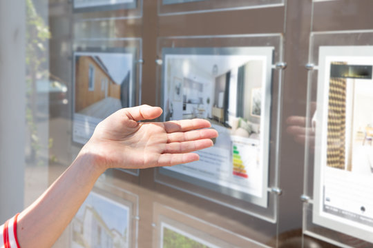 woman in front of real estate agent showcase window