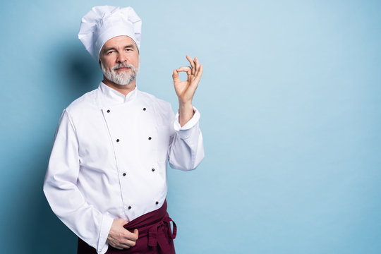 Mature professional happy man chef showing tasty ok sign isolated on light blue background.