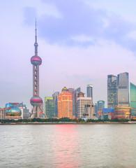 Fototapete - Illuminated Shanghai skyline at twilight
