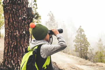 Child seen from behind with fluorescent backpack looks binoculars exploring nature of wild mountain forest. Family adventure discovery outdoor life. Young boy looking at the future. Positive concept