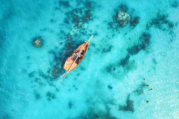 Poster Zanzibar Aerial view of the fishing boats in clear blue water at sunset in summer. Top view from drone of boat, sandy beach. Indian ocean. Travel in Zanzibar, Africa. Landscape with sailboats, sea. Seascape
