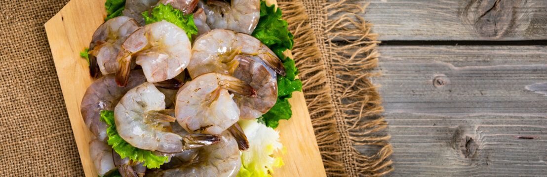 Large Raw Shrimp on Wooden Background. Selective focus.