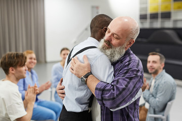 Side view  portrait of senior man hugging psychologist during therapy session in support group, copy space