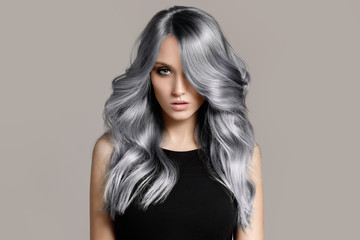 Door stickers Hair Salon Beautiful woman with long wavy coloring hair. Flat gray background.