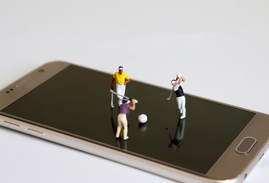 Miniature people playing golf on smart phones. The concept of online sports betting.