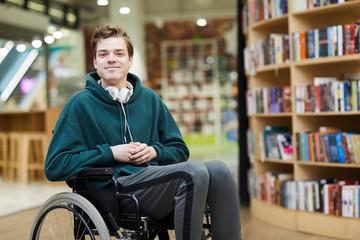 Content handsome young disabled student with headphones on neck siting in wheelchair and looking at camera in modern library or bookstore