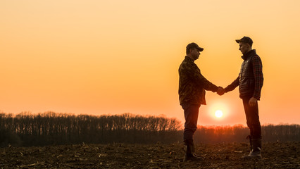 Two farmers on the field shake hands at sunset Wall mural