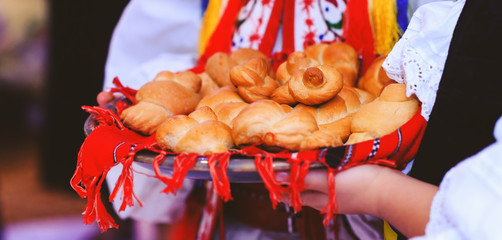 Baked buns or cakes in the hands of the children dressed in traditional costume. Bread in form of snails or pigeons in the red towel with elements of Romanian culture. Holiday scenic picture.