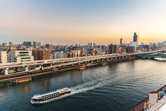 Sumida river with a cruise ship at sunset in Asakusa district Tokyo city, Japan.