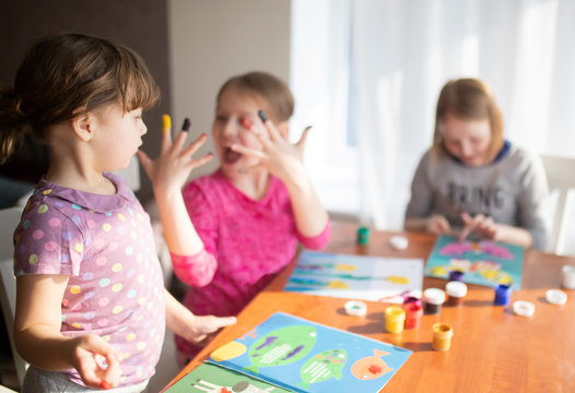 Three sisters little girls drawing with fingers on paper. Play, fun, childhood. Montessori school