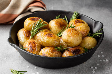 Fried (baked) whole small potatoes with rosemary and salt in a frying pan, ruddy crust, appetizing food