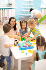 Educator helping kids playing with block constructor in daycare