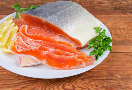 Partly sliced salted arctic char on dish on rustic table