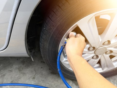 People hand are filling the tire pressure on the car wheel from automatic air filler at filling station.Copy Space.Safe driving or driving safety concept.