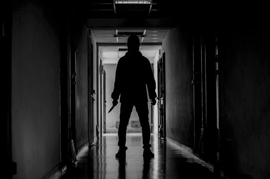 murder, kill and people concept - Criminal or murderer wearing a mask in silhouette holding knife inside a condo at crime scene.