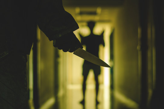 Close up of Hand with knife following young terrified man ,Bandit is holding a knife in hand. Threat Concept .