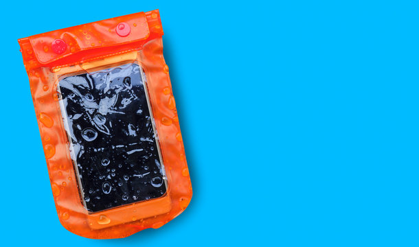 Orange waterproof mobile phone case with water droplets isolated on blue background.PVC zip lock bag protect mobile phone or important items from water.Concept for Songkran water festival in Thailand.