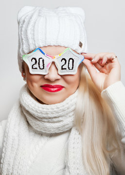"""Cheerful girl in a white hat and glasses with the inscription """"2020"""", on a white background"""