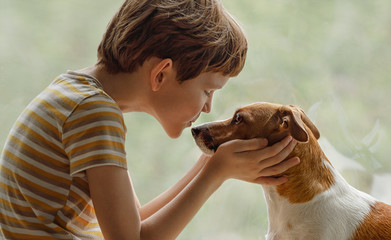 Child kisses the dog in nose on the window.