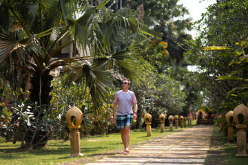 Young man travaler walking in a palm park on Ko Chang, Thailand in April, 2018 - Best travel destination for happiness