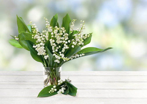 Bouquet of flowers and leaves lily of the valley ( Convallaria majalis ) in small glass on white wooden table on blur garden background