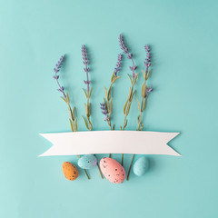 Easter composition made with lavander flowers and eggs on bright blue background with ribbon copy space. Creative minimal holiday concept.