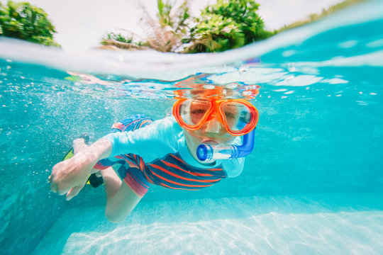 little boy swim underwater with mask in tropical resort