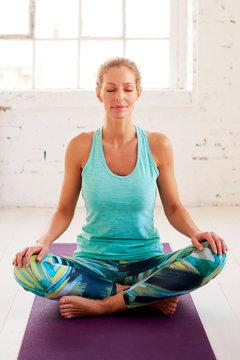 Beautiful woman meditating after yoga workout